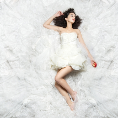 Young caucasian bride lying on a white cloud like fabric and holding a bitten apple. photo