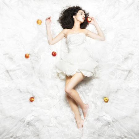 Caucasian girl sleeping on white fabric after eating an apple. Fairy-tale theme