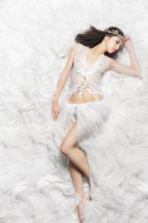 Young Caucasian girl is in a seductive sleeping pose. She is lying on a white fabric. Photographed from above. photo