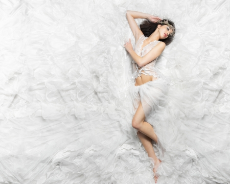 Cucasian girl from above in dream like pose while lying on bed of white fabric