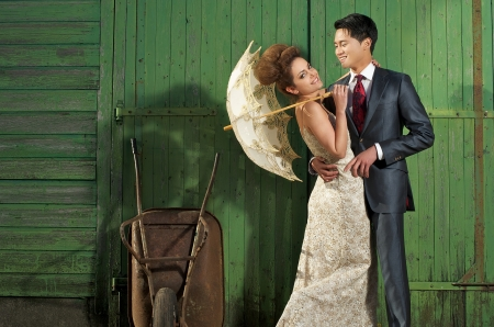 Bride and groom happy in eachothers arms posing outside against a green wall. Bride is wearing fashionable vintage wedding dress. photo