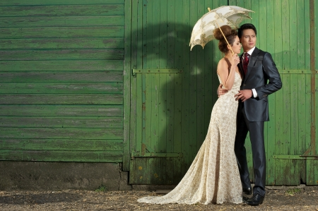 Handomse man with beautiful bride, wearing vintage wedding dress outdoors. photo