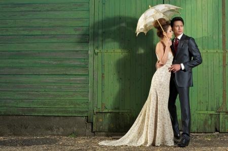 bridal couple: Handomse man with beautiful bride, wearing vintage wedding dress outdoors.