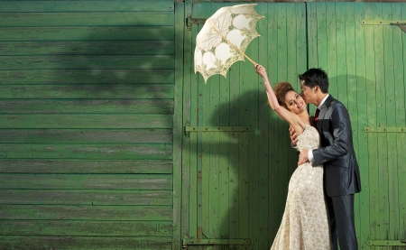 wedding portrait: Fun image of a beautiful bride in vintage wedding dress being kissed by a handsome man on a farm