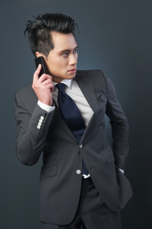 Asian businessman posing with mobile phone. Photographed against a grey background. photo