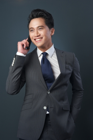 Handsome asian businessman smiling and talking on the phone. photo