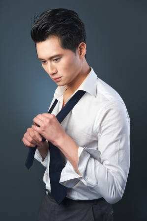 adjust: Portrait of an Asian businessman tieing his tie