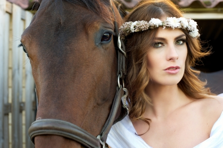 Landscape image of a beautiful female fashion model and her horse photo