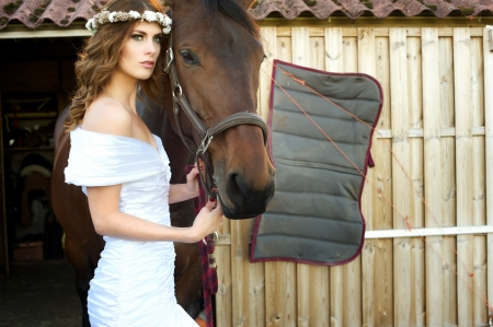 Beautiful landscape image of a bride and her friendly horse. She is wearing a white wedding dress and flowers in her hair photo