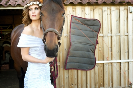 A beautiful bride is posing outside with her horse. She is wearing a white wedding dress and fliowers in her hair. photo