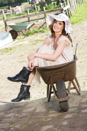 Fun image of a smiling fashion girl in a wedding dress and sitting in a wheelbarrow on a farm photo