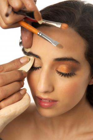 mujer maquillandose: Maquillaje Beng aplicada en la muchacha hermosa. Aislado sobre fondo blanco Foto de archivo