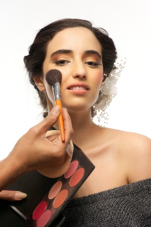 Isolated image of beautiful female model having her make up applied with brush photo
