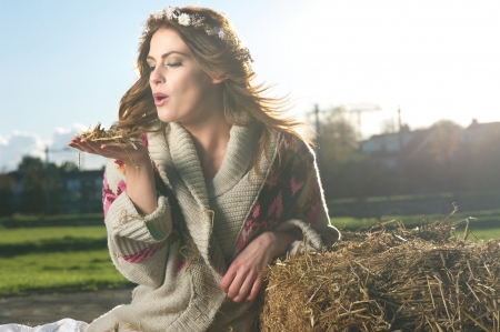 girl blowing: Fun image of a beautiful European girl blowing hay while outside