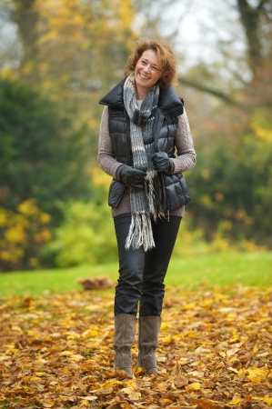40s adult: A beautiful autumn woman holding her scarf and smiling. Standing in the yellow leaves Stock Photo