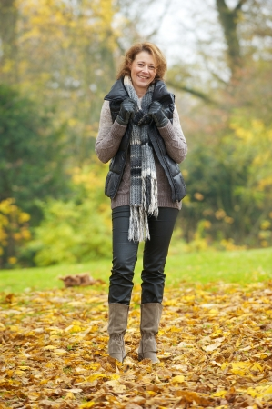 mid age: European woman in autumn. Walking on yellow leaves and smiling