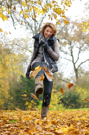 women in boots: A woman kicking yellow leaves in autumn. She is smiling and holding her scarf.