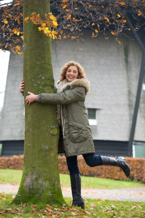 A beautiful middle age woman tree hugging in Europe photo