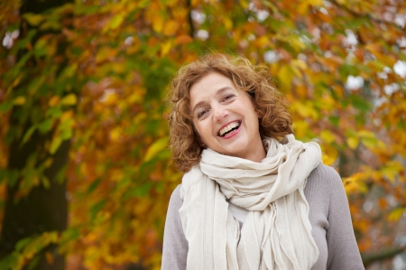 40s: Mature woman smiling in autumn. A beautiful yellow leaves background