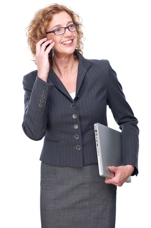 Business woman isolated on white background. She is talking on a mobile phone and holding a laptop photo