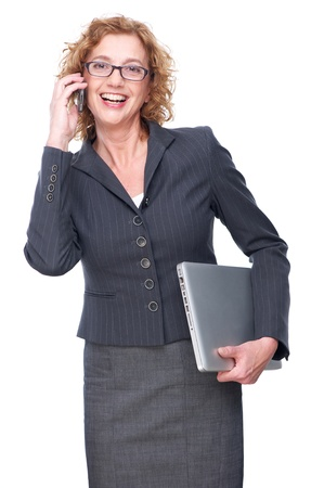 Portrait of a business woman with glasses isolated on white background. She is talking on the phone and holding laptop photo