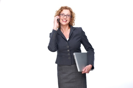 Portrait of a European business woman talking on the phone. She is smiling and has a latop in hand. The business woman is isolated on a white background Stock Photo - 16491962