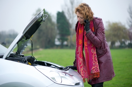roadside assistance: Caucasian woman calling for road side assistance on her mobile phone. The hood is up on her car aand there is engine trouble. Stock Photo