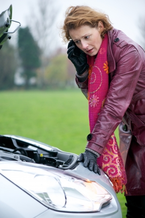 Caucasian woman calling for help on her mobile phone. She is looking under the hood of a broken down car. photo