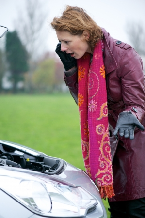 Worried Caucasian woman on mobile phone. She is looking under the hood of her broken down car with engine failure photo