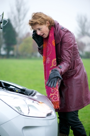 Stressed Caucasian woman calling for roadside assistance. She is looking under the bonnet and talking to technical support on her mobile phone. photo