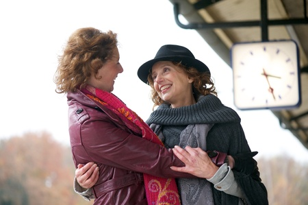 Friendly hug from two european women at an outdoor train station platform. photo