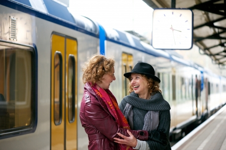 Two mature women friends welcoming each other with a smile and a warm embrace at an outdoor train station platform