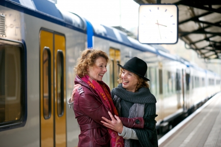 greets: Happy smile for two friends as they greet each other at an outdoor train station platform Stock Photo