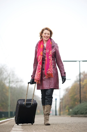 Happy Caucasian woman is smiling and walking on the train platform as she arrives at the trainstation. She is pulling her baggage photo