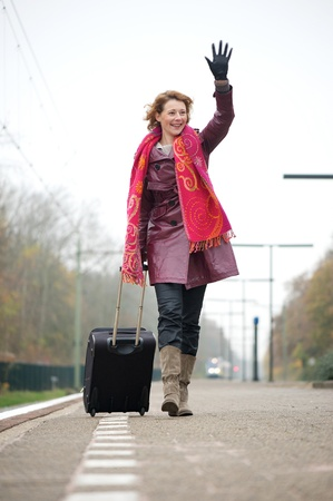 Woman waving goodbye. She is walking on an outdoor platform at a train station and carrying her luggage photo