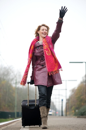 Woman waving hello as she arrives on an outdoor platform at the train station photo