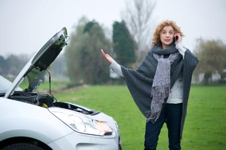 Donna sul telefono cellulare bisogno di avvisare circa la sua broekn giù auto