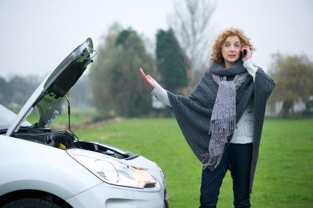 Woman on mobile phone needing advise about her broekn down car Imagens