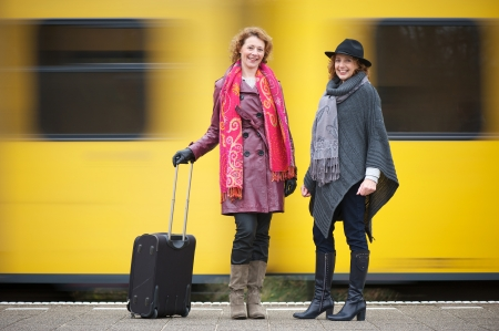 Two female friends are standing on the train station platform with luggage as a yellow train speeds past them in the background photo