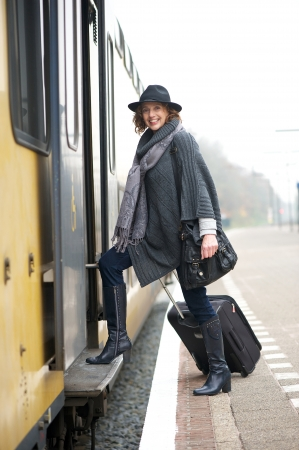 Traveling woman with suitcase luggage is boarding the train from the platform and smiling at the camera