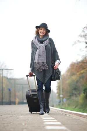 outoors: Happy smile from a traveling woman walking on the train station platform outoors and carrying her luggage