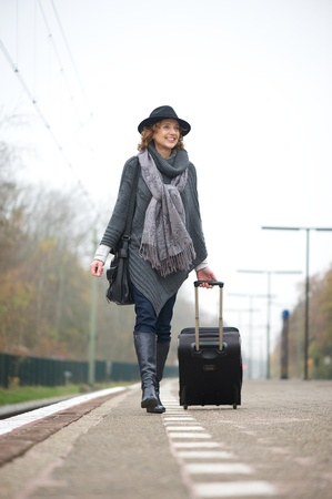 Commuting woman holding her luggage on a train station platform. photo