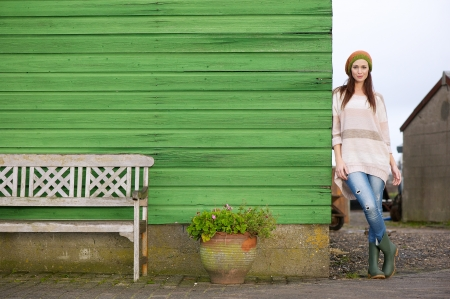 seasonal clothes: Horizontal portrait of a beautiful young Caucasian woman standing outside against a green wooden wall. Possibility for copy space