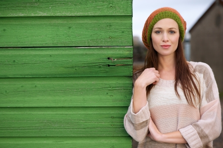 seasonal clothes: Close up portrait of a beautiful woman leaning against a green wooden wall outdoors. Possibilty for copy space Stock Photo
