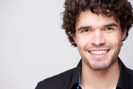 uomo felice: Ritratto orizzontale di un giovane uomo bello caucasico sorridente modello maschile guardando Posiibility fotocamera per lo spazio della copia Archivio Fotografico