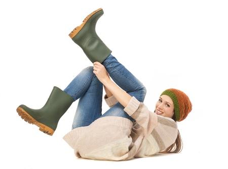 Mujer joven sonriendo y poniendo las botas de jardinería aislados en fondo blanco
