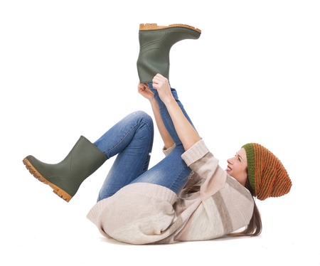 putting on: Beautiful young woman isolated on white background and putting on gardening boots  Stock Photo