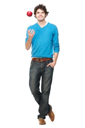 fruit stand: Full length portrait of a handsome casual young man throwing an apple up. Isolated on white background