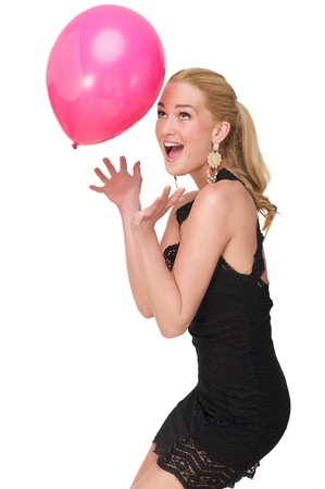 seductive expression: Beautiful young blond woman catching a pink balloon with a heart on it. She is wearing a black dress and has a surprised expression on her face. Isolated on white background