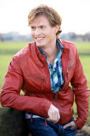 Handsome young blonde male relaxing outdoors. Casual guy wearing a red leather jacket and blue jeans and shirt. He is leaning against a fence outdoors and smiling while looking away. photo